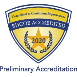 "A gold, triangular badge with a dark gold star, blue trim, and white text that says ""Committed to Continuous Improvement. BHCOE Accredited 2020, Preliminary Accreditation"""