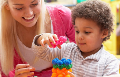 young woman stacking colorful blocks with curly-haired toddler boy