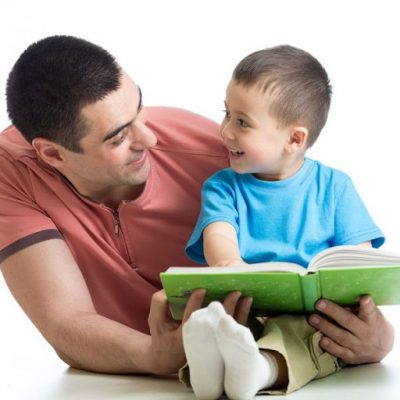 Father in red shirt with black hair, smiling with his arm around his toddler son with black hair and a blue shirt, reading a book with a green cover