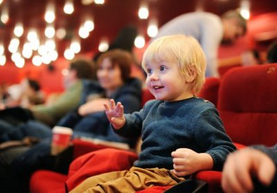 toddler boy with blonde hair and blue shirt smiles in movie theater of red seats and warm soft lights; other people are blurred in background.