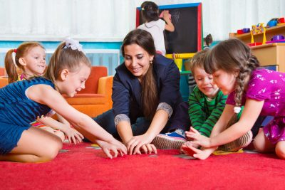 teacher sitting on red carpet with 4 preschool-aged children playing a hands-over-hands game